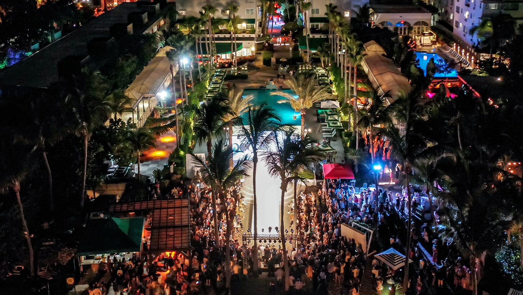 Nighttime aerial image of Kimpton Surfcomber during an Ocean Drive Swim Week runway show